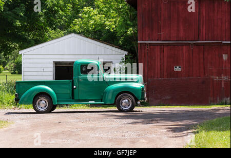 Moravia, New York - June 2016. Old classic truck in front of a red barn. - Stock Photo