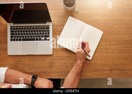Close up of man writing notes in personal notebook with a laptop and cup of coffee on table. - Stock Photo