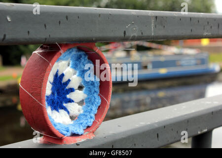 A Crochet canal wheel and bunting attached to a foot bridge over the Leeds and Liverpool canal in Blackburn Lancashire. - Stock Photo