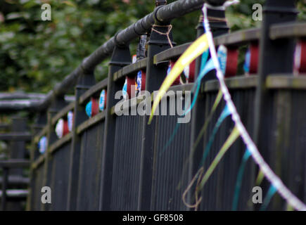 Crochet canal wheels and bunting attached to a foot bridge over the Leeds and Liverpool canal in Blackburn Lancashire. - Stock Photo