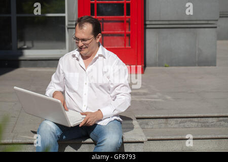 Business man using mobile phone red classic English telephone box - Stock Photo