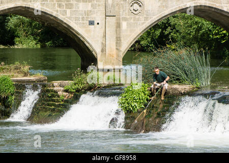 Fisherman on Bathampton Weir with rod and net. Amateur angler scoops fish into net on waterfall in River Avon - Stock Photo