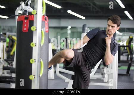 Young man exercising at gym - Stock Photo