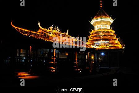 Drum Tower and Rain Bridge at Night, Zhaoxing, Guizhou, China - Stock Photo