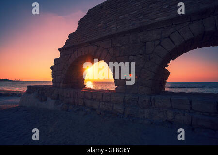 Remains of the ancient Roman aqueduct in ancient city Caesarea at sunset, Israel. - Stock Photo