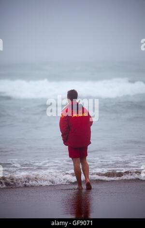 Male lifeguard from the Royal National Lifeboat Institute guards over surfers on Whitsand Bay, Cornwall, England, - Stock Photo