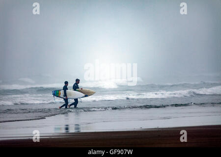 Two cornish surfers returning from the surf at Whitsand Bay located in Cornwall, England, UK as the mist rolls in. - Stock Photo