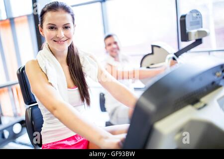 PROPERTY RELEASED. MODEL RELEASED. Portrait of young woman with napkin around her neck in gym, smiling. - Stock Photo