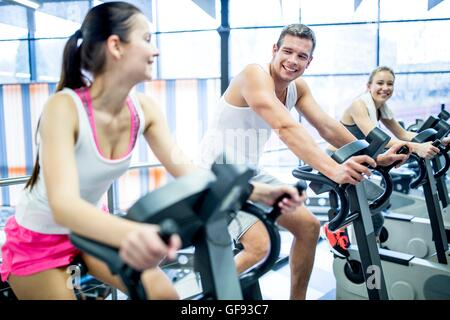 PROPERTY RELEASED. MODEL RELEASED. Young men and women working out on exercise machines in gym, smiling. - Stock Photo