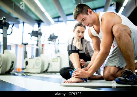 PROPERTY RELEASED. MODEL RELEASED. Young man applying ice pack on young woman's ankle in gym. - Stock Photo