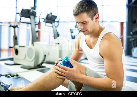 PROPERTY RELEASED. MODEL RELEASED. Young man holding ice pack on injured knee in gym. - Stock Photo