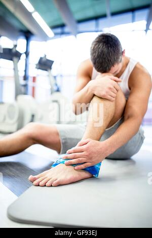 PROPERTY RELEASED. MODEL RELEASED. Young man holding ice pack on injured ankle in gym. - Stock Photo
