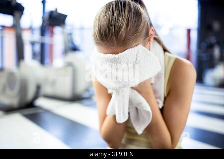 PROPERTY RELEASED. MODEL RELEASED. Young woman wiping her sweat with towel after exercising in gym. - Stock Photo