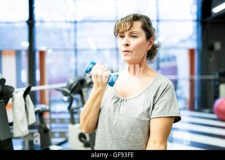PROPERTY RELEASED. MODEL RELEASED. Senior woman holding dumbbell in gym. - Stock Photo