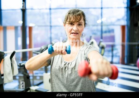 PROPERTY RELEASED. MODEL RELEASED. Portrait senior woman holding dumbbell in gym. - Stock Photo