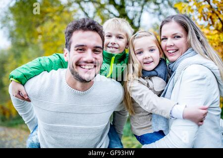 MODEL RELEASED. Parents carrying their children in autumn, portrait, smiling. - Stock Photo