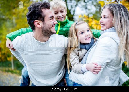 MODEL RELEASED. Parents carrying their children in autumn, laughing. - Stock Photo