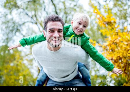 MODEL RELEASED. Father carrying son piggyback in autumn, smiling, portrait. - Stock Photo