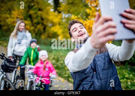 MODEL RELEASED. Smiling man taking photo of family. - Stock Photo