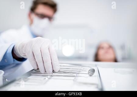 MODEL RELEASED. Dentist with angled mirror in dentist clinic. - Stock Photo