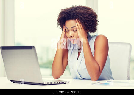 african woman with laptop at office - Stock Photo