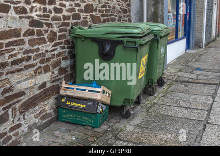 A couple of industrial recycling wheely bins and waste boxes outside a shop in Truro, Cornwall. Rubbish bins outside - Stock Photo