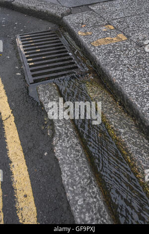 Street drainage / gutter in Truro, Cornwall. Visual metaphor for 'money down the drain' and water waste / wasting - Stock Photo