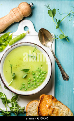 Light summer green pea cream soup in bowl with sprouts, bread toasts and spices - Stock Photo
