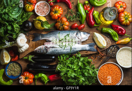 Raw uncooked seabass fish with vegetables, grains, herbs and spices on chopping board over rustic wooden background - Stock Photo