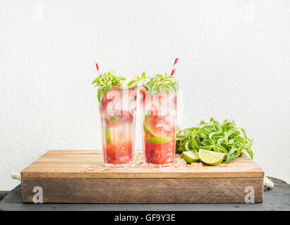 Strawberry mojito summer cocktails with mint and lime in tall glasses - Stock Photo