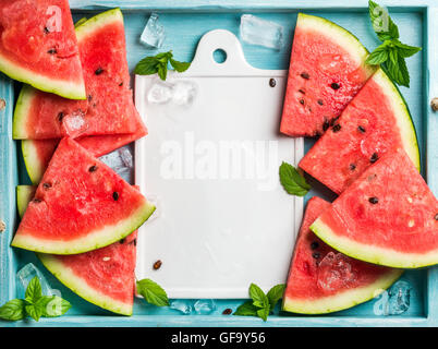 Watermelon slices with ice cubes and mint leaves on blue wooden background, white ceramic board in center. Top view, - Stock Photo