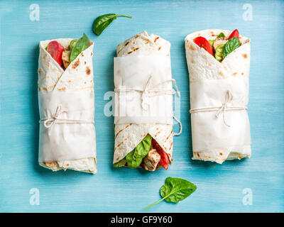 Healthy lunch snack. Tortilla wraps with grilled chicken fillet and fresh vegetables - Stock Photo