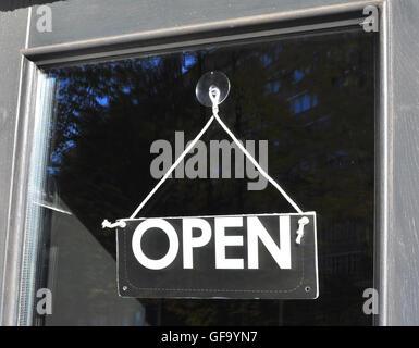 Open sign hanging on the door - Stock Photo