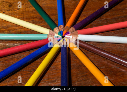 crayons group forming concentric circles on wooden background - Stock Photo