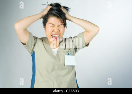 female model attractive woman on plain background with copy space frustrated pulling hairs - Stock Photo