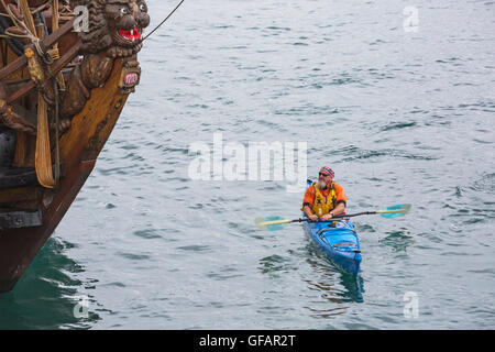 Swanage, Dorset, UK. 30th July, 2016. Kayaker passes the replica 1703 Russian frigate Shtandart, stopping to look, - Stock Photo