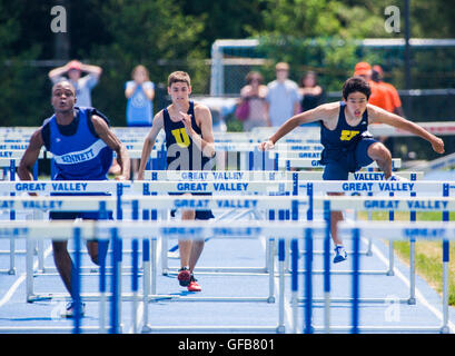 Male high school students compete in hurdles event at the Southern Chester County League, Track & Field Championship - Stock Photo