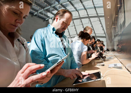 People try out iPads at the Apple Store on Broadway in New York. March 2010. - Stock Photo