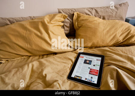 Apple iPad device displaying the New York Times newspaper's nytimes.com homepage on a bed, 2010. - Stock Photo