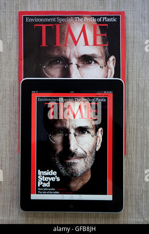 Apple iPad displaying the Time Magazine application on a print version of the magazine with Steve Jobs on the cover, - Stock Photo
