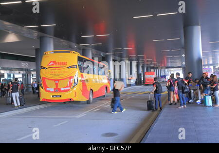 People wait for buses at Kuala Lumpur airport 2 bus terminal. - Stock Photo