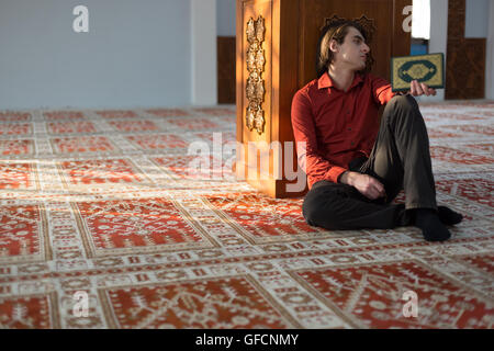Young muslim man is praying in the mosque - Stock Photo
