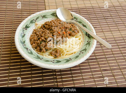 spaghetti in bowl with meat sauce and spoon on bamboo mat - Stock Photo