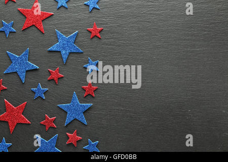 Red and blue stars on slate background - Stock Photo