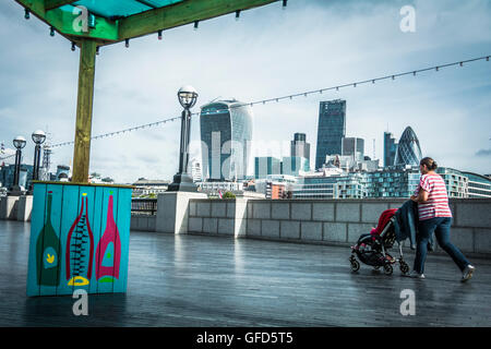 A woman pushes a buggy near More London in the Scoop, Queen's Walk, London SE1 - Stock Photo