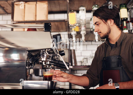 Side view of male barista preparing espresso at coffee shop. Young man in apron making coffee using coffee maker - Stock Photo