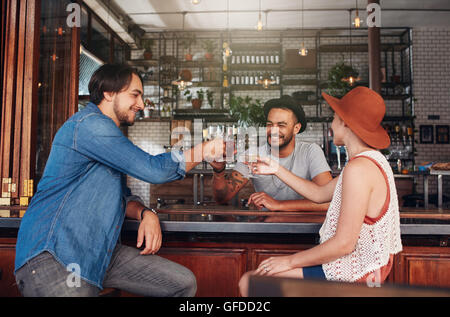 Three young people sitting in the restaurant and having a toast. Group of friends at a cafe having a drink and toasting. - Stock Photo