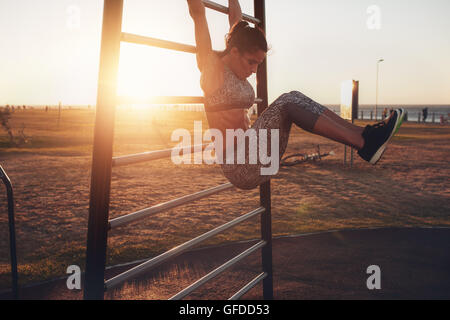Candid shot of real healthy and fit woman performing hanging leg raises on outdoor fitness station in sunset at - Stock Photo