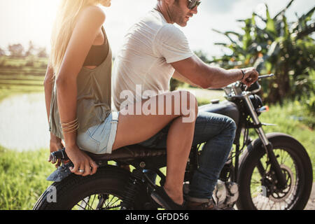 Cropped shot of young man riding on a motorcycle with girlfriend on country road. Man and woman riding on a motorcycle. - Stock Photo