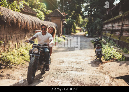 Shot of young couple on motorcycle on country road. Man riding on a motorbike with girlfriend on village road. - Stock Photo